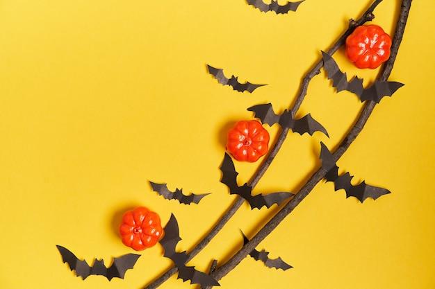 Fond d'halloween, orange en plastique décoratif citrouille en papier noir chauve-souris branche sèche bâton carton jaune