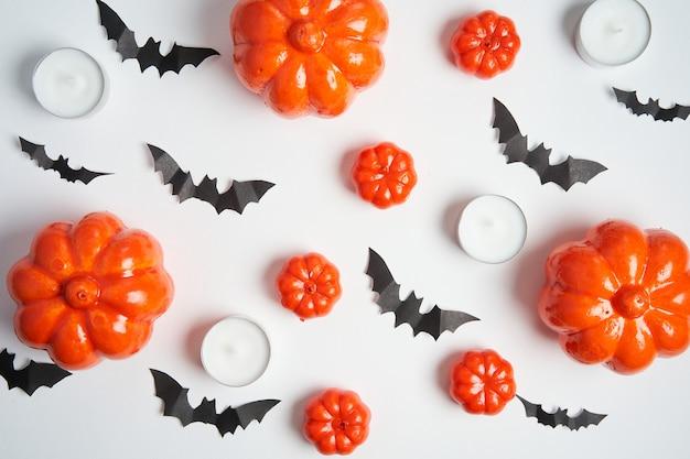 Fond d'halloween, potiron en plastique décoratif orange chauve-souris en papier noir bougie ronde carton blanc