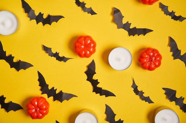 Fond d'halloween, potiron en plastique décoratif orange chauve-souris en papier noir bougie ronde en carton jaune