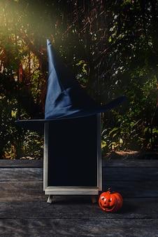 Fond d'halloween spooky citrouille, chapeau de sorcière, tableau noir sur bois