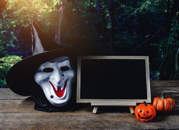 Fond d'halloween spooky pumpkin, masque de sorcière, tableau noir sur plancher de bois
