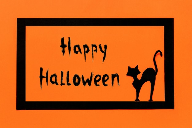Fond d'halloween. texte de chat en papier noir happy halloween dans un cadre noir sur fond orange.