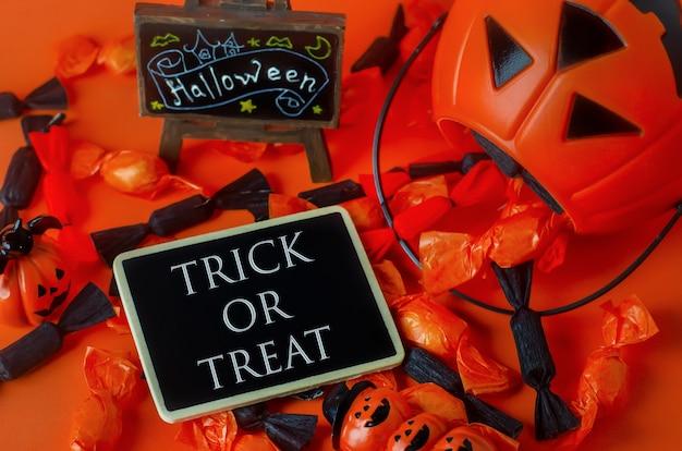 Fond d'halloween - trick or treat sur une étiquette en bois avec des bonbons noirs et orange