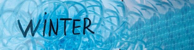 Fond d'hiver aquarelle. illustration à l'aquarelle de l'art abstrait avec l'inscription hiver dans les tons bleus, bannière.