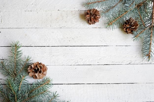 Fond d'hiver avec des branches de pin, cônes, espace de copie en bois blanc, carte de fête, vacances saisonnières