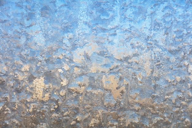 Fond d'hiver sur un verre transparent d'une fenêtre avec une texture gelée. fond de texture abstraite