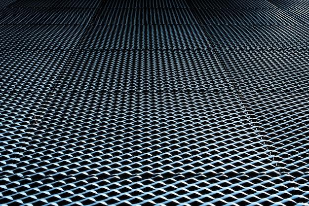 Fond industriel avec texture métallique éclairée par une lumière intense et des ombres intenses