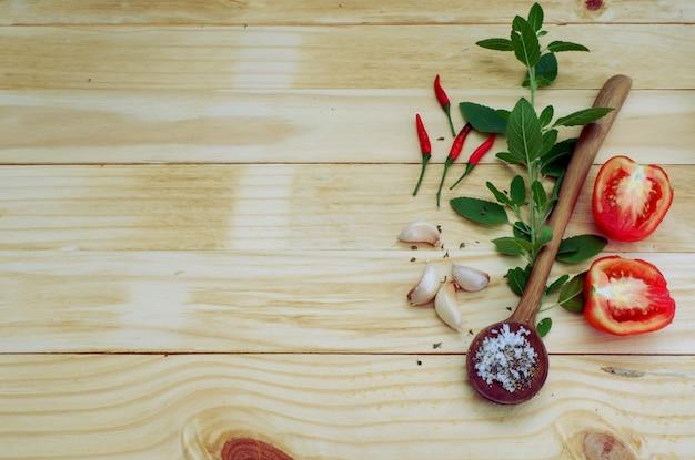 Fond d'ingrédients épicés piment, sel, poivre, ail, tomate, sur le dessus en bois
