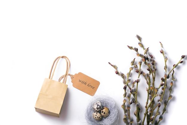 Fond isolé de pâques avec des œufs de caille dans le nid avec branche de saule et coffret cadeau avec amour .espace libre pour votre texte.