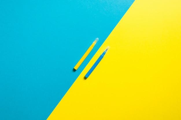 Fond jaune et bleu coloré avec deux stylos