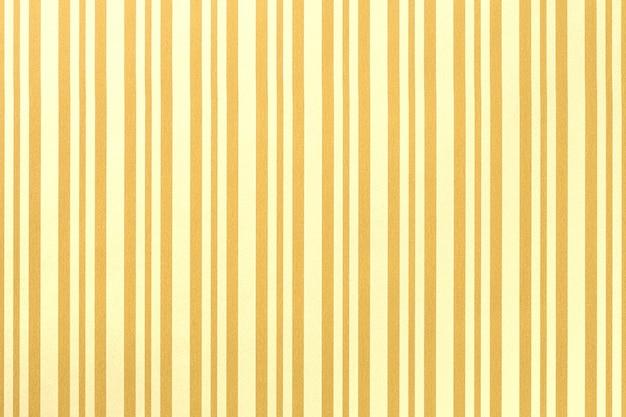 Fond jaune clair et doré de papier d'emballage rayé,