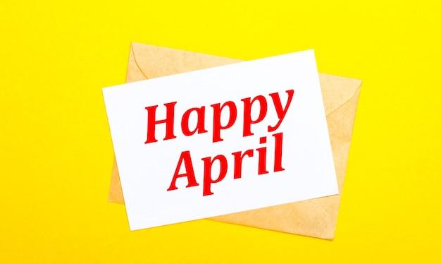 Sur fond jaune, une enveloppe et une carte avec le texte happy april