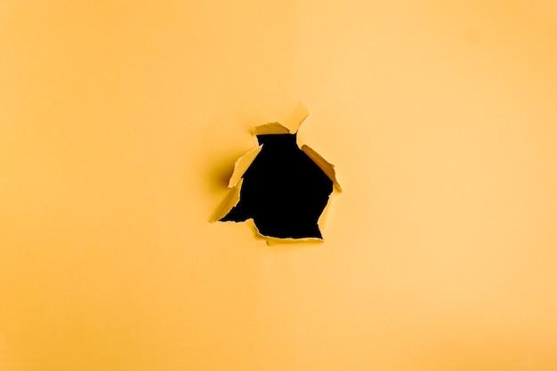 Fond jaune et noir du trou dans le papier cartonné avec espace copie