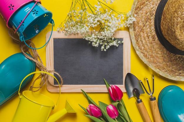 Fond jaune avec des outils d'ardoise et de jardinage