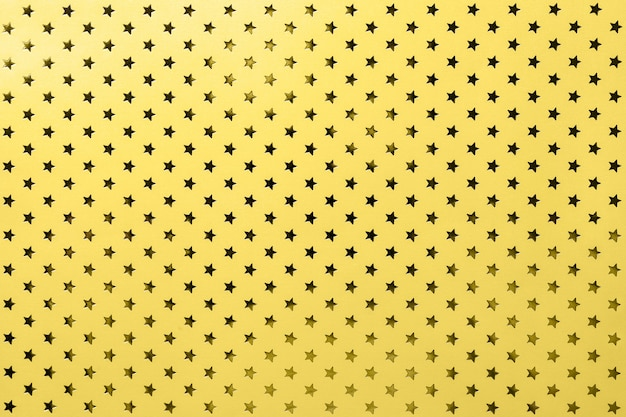 Fond jaune de papier d'aluminium avec un motif d'étoiles d'or