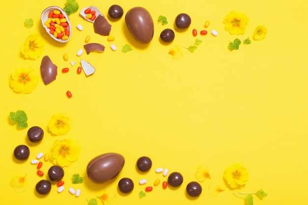 Fond jaune de pâques avec des œufs en chocolat, des bonbons et des spri