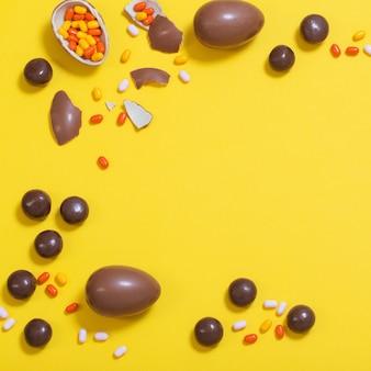 Fond jaune de pâques avec des oeufs de chocolat et des bonbons