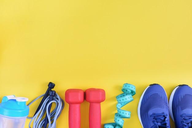 Sur un fond jaune photographié des baskets, une corde à sauter, des haltères et une bouteille. espace copie