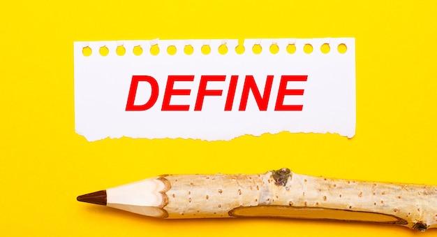 Sur un fond jaune vif, un grand crayon en bois et une feuille de papier déchirée avec le texte define