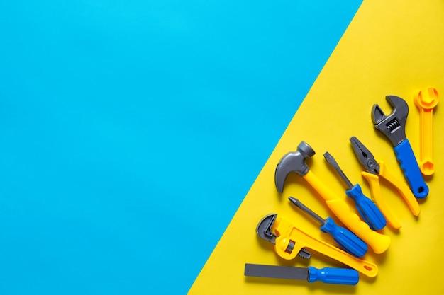 Fond de jouets. vue de dessus des outils jouets sur fond jaune bleu avec espace de copie pour le texte.
