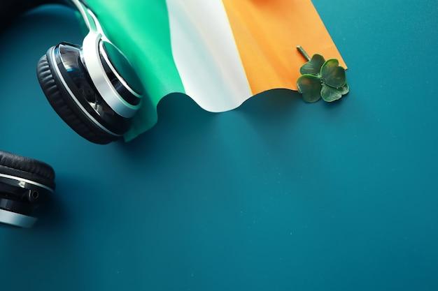 Fond de jour de saint patrick avec le drapeau de l'irlande. fête religieuse chrétienne. trèfle à quatre feuilles symbole de bonne chance.
