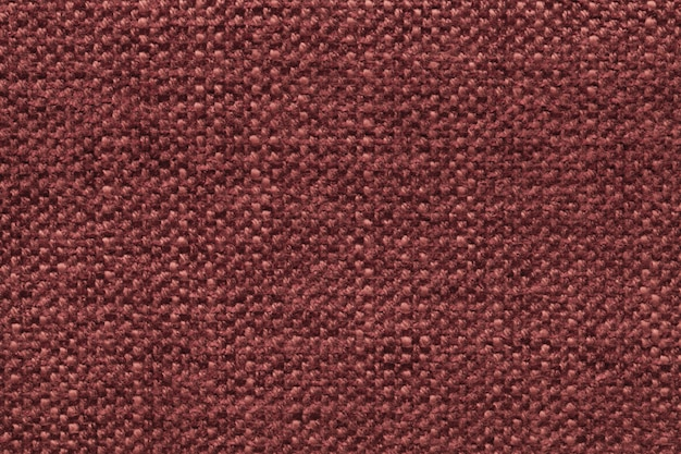 Fond en laine tricoté rouge foncé avec un motif de tissu doux et moelleux. texture du textile agrandi.