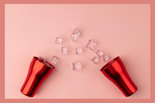 Fond large rose avec une tasse rouge et de la glace sur le sol