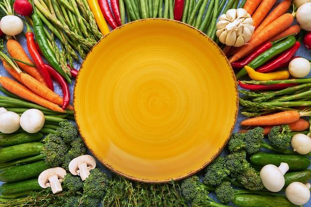 Fond de légumes avec une assiette jaune vide au milieu. carottes, tomates, asperges, brocoli, piment, haricots verts. vue de dessus. alimentation biologique.