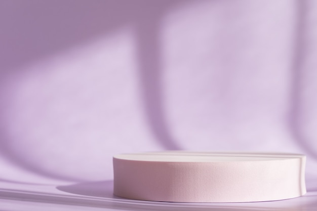 Fond lilas avec podium rond rose, affichage. présentation du produit cosmétique avec des ombres
