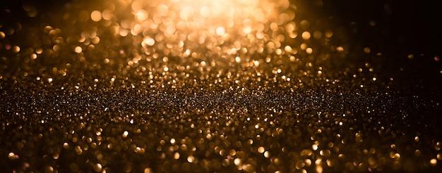 Fond de lumières scintillantes or et noir abstrait défocalisé