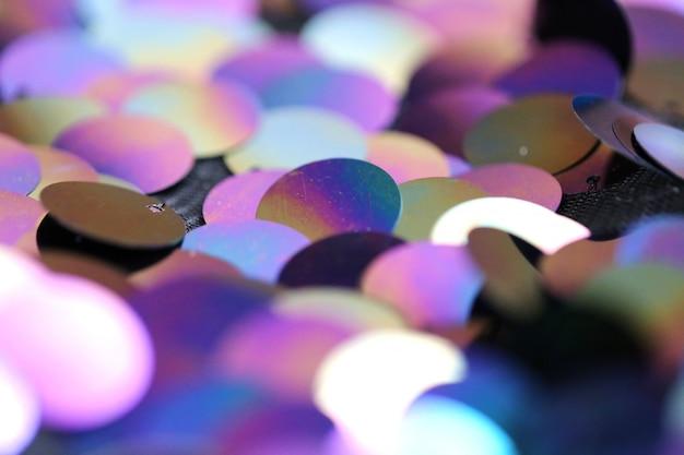 Fond de macro de paillettes. grands sequins holographiques dans les tons violets et bleus