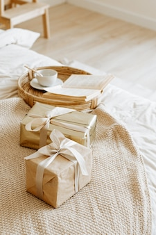 Fond de maison avec des coffrets cadeaux avec des cadeaux emballés dans du papier kraft et décorés d'un beau ruban.