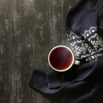 Fond de maison d'hiver confortable, tasse de thé chaud et pull tricoté chaud sur table noire.
