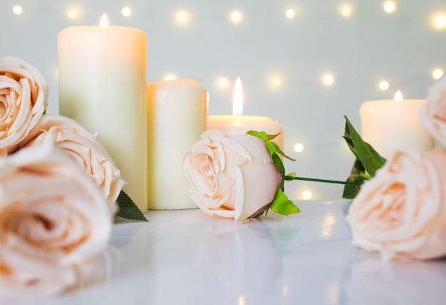 Fond de mariage et de la saint-valentin avec des roses beiges et des bougies contre la lumière bokeh, concept doux et propre.