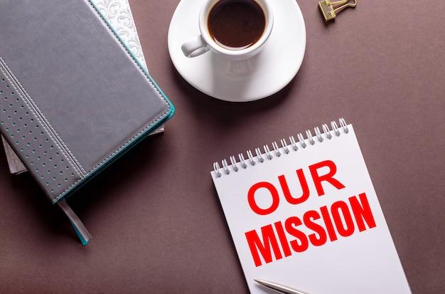 Sur fond marron, des agendas, une tasse de café blanche et un cahier avec notre mission