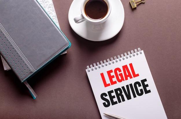 Sur fond marron, des agendas, une tasse de café blanche et un cahier avec service juridique