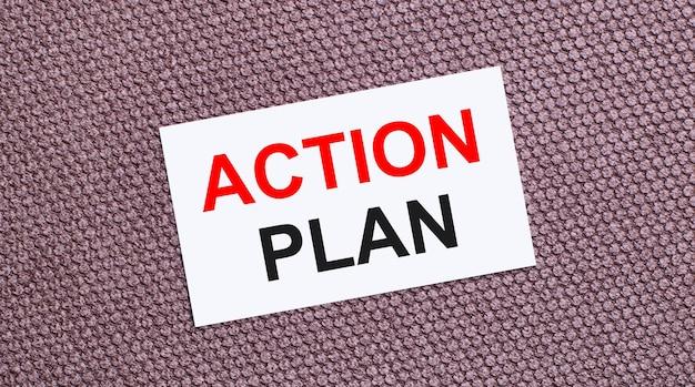 Sur fond marron, une carte rectangulaire blanche avec le texte plan d'action