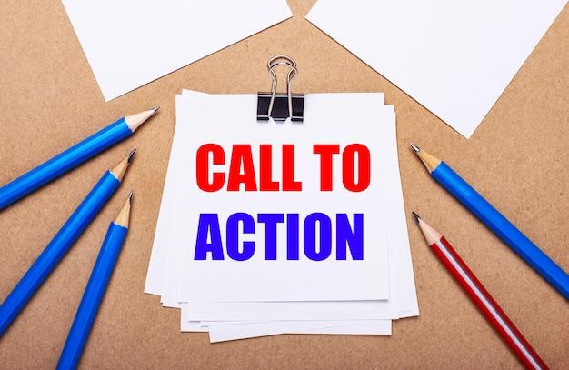 Sur un fond marron clair, des crayons bleus et rouges et du papier blanc avec le texte appel à l'action