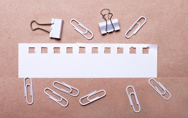 Sur un fond marron, des trombones blancs et une bande de papier blanc déchirée avec un espace pour insérer du texte. modèle