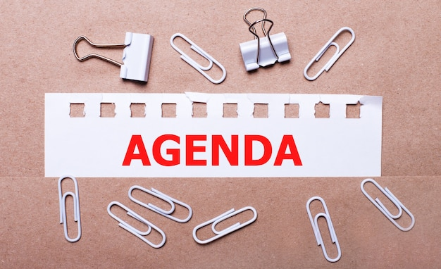 Sur un fond marron, des trombones blancs et une bande de papier blanc déchirée avec le texte agenda