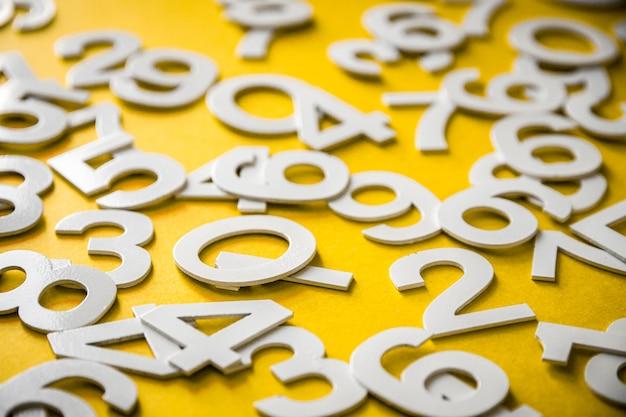 Fond de mathématiques fait avec des nombres solides sur une planche. isolé sur jaune