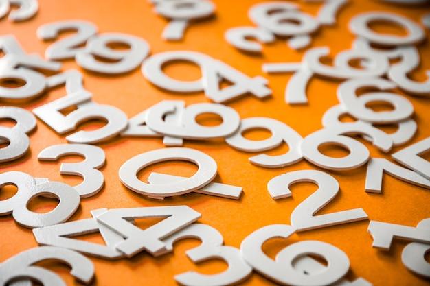 Fond de mathématiques fait avec des nombres solides sur une planche. isolé sur orange
