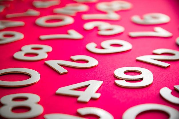 Fond de mathématiques fait avec des nombres solides sur une planche. isolé sur rose