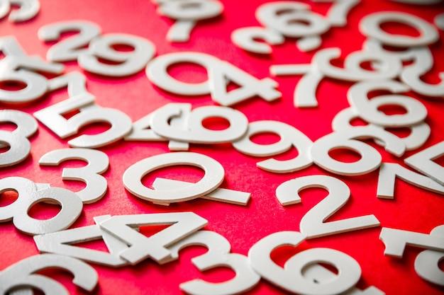 Fond de mathématiques fait avec des nombres solides sur une planche. isolé sur rouge