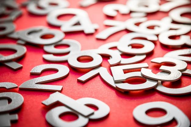 Fond De Mathématiques Fait Avec Des Nombres Solides Sur Une Planche. Isolé Sur Rouge Photo Premium
