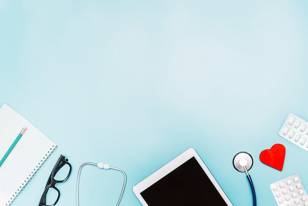 Fond sur la médecine avec le stéthoscope, la médecine, la tablette et le bloc-notes