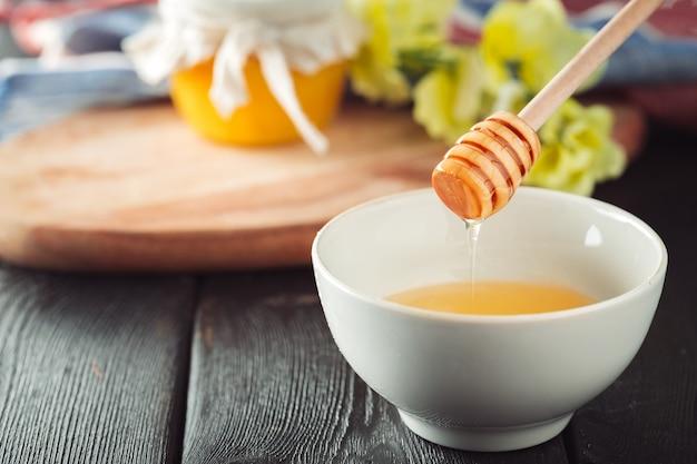 Fond de miel. miel doux en pot de verre sur fond en bois.