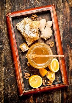 Fond de miel. miel frais avec du citron et du gingembre dans un vieux plateau. sur fond de bois.