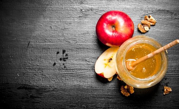 Fond de miel. miel en pot avec des tranches de pommes mûres et de noix.