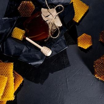 Fond de miel. nid d'abeille naturel et cuillère en bois. sur table rustique noire.